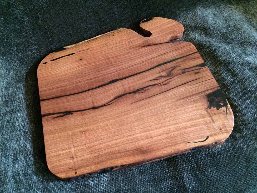 cutting board made from mesquite wood with black resin fill and natural edge