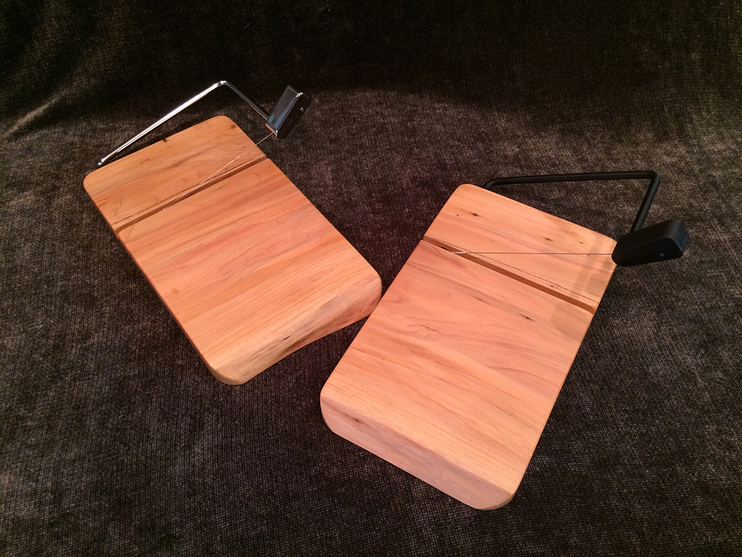 pair of mesquite wood cheese slicers with black and silver hardware